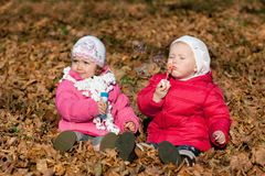 Two girl blowing bubbles outdoors Royalty Free Stock Image