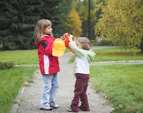 Two girl with cap. Two child play with cap in autumn Stock Photo