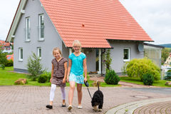 Two girl or children walking with dog. Two young girls or children - sisters - walking with the dog Royalty Free Stock Images