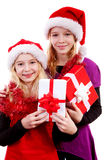Two girl with christmas hat and presents. Posing over white background Stock Photo