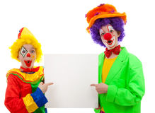 Two girl clowns holding empty text board. Over white background Stock Image