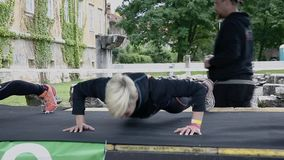 Two girl coaches showing push ups stock video footage