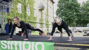 Two girl coaches showing push ups. Guiding training on stage stock video