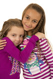 Two girl counsins wearing christmas pajamas hugging each other Stock Images