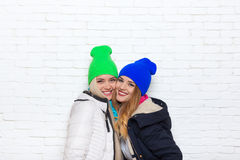 Two girl couple smile wear winter colorful hats jacket Royalty Free Stock Photos