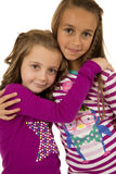 Two girl cousins wearing christmas pajamas hugging each other Royalty Free Stock Photos