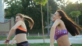 Two girl doing active exercise with smile on faces on the grass. 4K. Two girl doing active exercise with smile on faces on the grass in the morning in 4K stock video