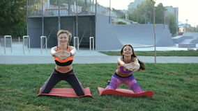 Two girl doing active exercise with smile on the grass in the morning in 4K.  stock footage