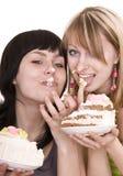 Two girl eating chocolate cake. Stock Image