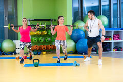 Two girl exercising at the gym with a personal trainer. Two girl exercising at the gym with a personal trainer Royalty Free Stock Image