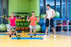 Two girl exercising at the gym with a personal trainer. Two girl exercising at the gym with a personal trainer Stock Photography