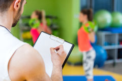 Two girl exercising at the gym with a personal trainer. Two girl exercising at the gym with a personal trainer Stock Photos