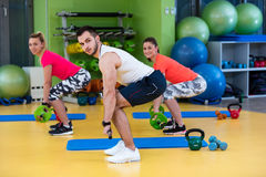 Two girl exercising at the gym with a personal trainer. Two girl exercising at the gym with a personal trainer Royalty Free Stock Photo