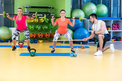 Two girl exercising at the gym with a personal trainer. Two girl exercising at the gym with a personal trainer Stock Photo