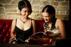 Two girl-friends. Two pretty girl-friends reading magazines Stock Image