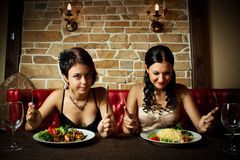 Two-girl friends. Two pretty glamour girl preparing to have a dinner Stock Photography