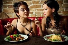 Two-girl friends. Two pretty girl-friends eating at a restauraut Royalty Free Stock Image