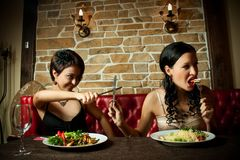 Two girl-friends. Two pretty girl-friends sitting at a restaurant Royalty Free Stock Image