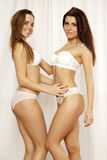 Two  girl friends - blond and brunette in white lingerie Stock Photography