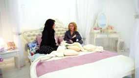 Two girl friends chat and gossip, sitting on bed in bright bedroom late at night. stock video