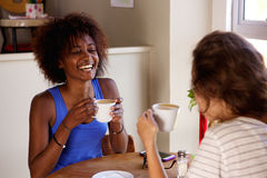 Two girl friends enjoying a cup of coffee at cafe Royalty Free Stock Image