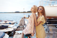 Two girl friends enjoying the evening sunset in the port Stock Photos