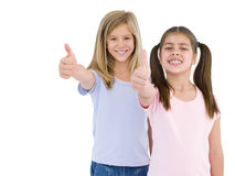 Two girl friends giving thumbs up smiling Royalty Free Stock Photography