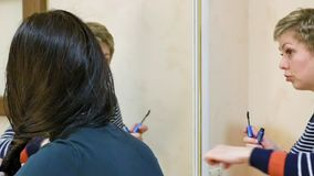 Two girl friends gossiping in dressing makeup room. Two beautiful girl friends gossiping chitchatting in dressing make-up room restroom while making up and stock footage