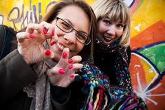 Two girl friends having fun and laughing. Two pretty girl friends having fun and laughing on the street. On graffiti background Royalty Free Stock Image