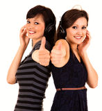 Two girl friends in heaphones with thumbs up Stock Image