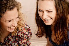 Two girl friends laughing gleefully royalty free stock photos
