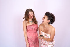 Two girl friends laughing and having fun looking at smart phone . Technology, Internet , communication Stock Images