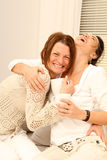 Two Girl Friends laughing loud. Two girl friends sitting on the couch and laughing loud stock photos