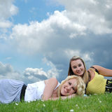 Two girl friends laying in grass Royalty Free Stock Photos