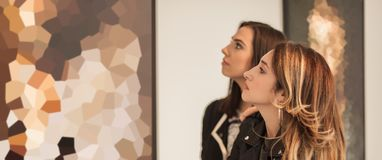 Two girl friends looking at modern painting in art gallery stock photos