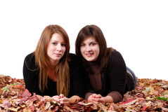 Two girl friends lying in autumn leaves Stock Photos