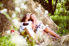 Two girl-friends lying on hay stack Royalty Free Stock Photography