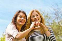 Two girl friends. Making a finger heart Stock Photos