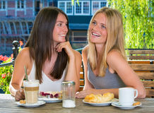 Two girl friends in outdoor cafe Stock Image