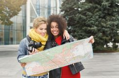 Two girl friends outdoors with paper city map. Two girls with paper map outdoors. Female friends walking around late autumn city, taking photos and having fun Stock Images