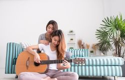Free Two Girl Friends Playing Guitar At Sofa In Living Room Near Wind Royalty Free Stock Images - 118118599