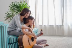Two girl friends playing guitar at sofa in living room near wind Royalty Free Stock Photography