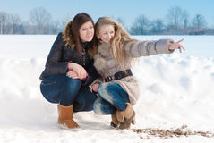 Two girl friends pointing in winter snow. Two young women pointing and looking in winter snow background Stock Image
