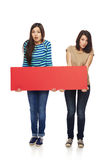 Two girl friends with red banner. Women billboard sign. Fill length of two surprised women holding blank red banner, over white background Royalty Free Stock Photos