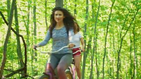 Two girl friends ride bicycles in the green forest on a Sunny day. Telephoto shot stock video