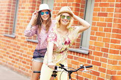 Two girl friends riding tandem bicycle Stock Images