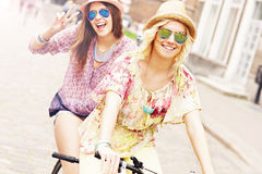 Two girl friends riding tandem bicycle royalty free stock photos
