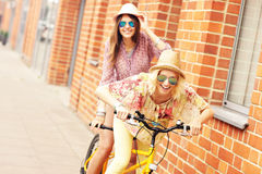Two girl friends riding tandem bicycle Royalty Free Stock Image