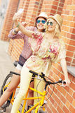 Two girl friends riding tandem bicycle Stock Image