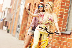 Two girl friends riding tandem bicycle Stock Photography
